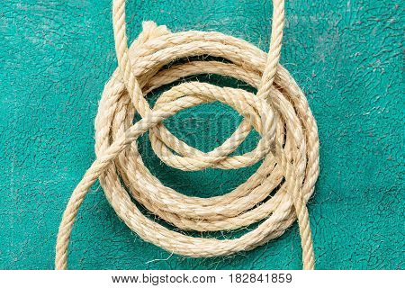 Ship rope knot on turquoise background. Top view.