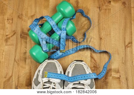 On the wooden floor are two dumbbells white sneakers and a centimeter