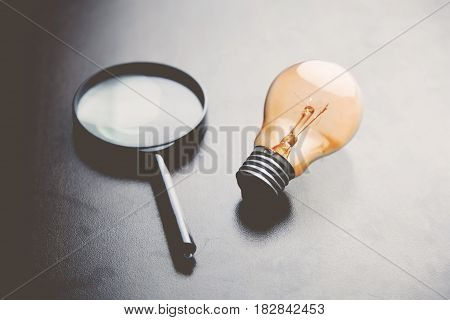Magnifying Glass and Light Bulb on table