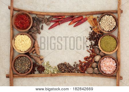 Spice and herb seasoning with cinnamon sticks forming an abstract border on natural hemp paper background.