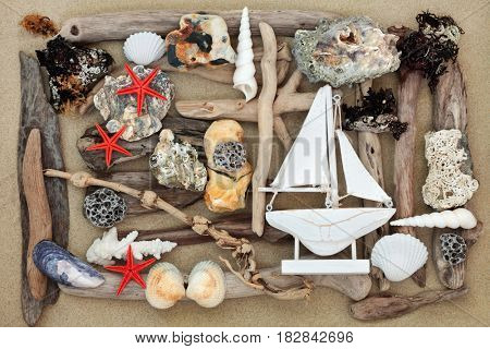 Beach art abstract with driftwood, seashells, rocks, seaweed and decorative sailing boat on sand background.