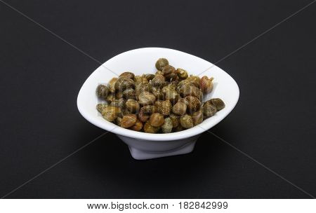 bowl with fresh capers isolated on black background