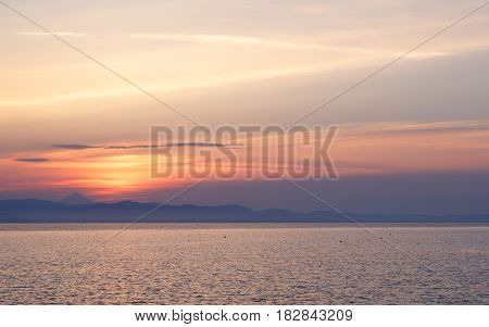 Early morning at dawn of the day with a calm blue sea overlooking the sky and mountains of the other shore Kassandra Greece