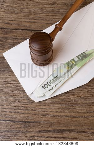 Hammer on envelope with money