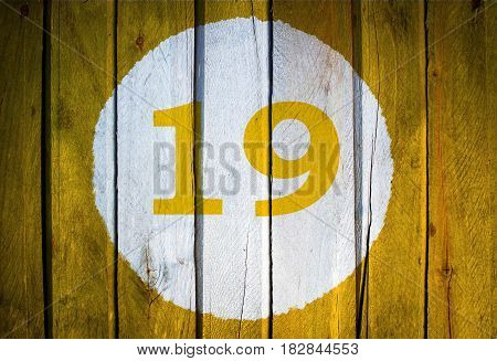 House Number Or Calendar Date In White Circle On Yellow Toned Wooden Door Background. Number Ninetee