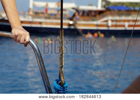 woman standing next to a boat's railing with people swimming in the background
