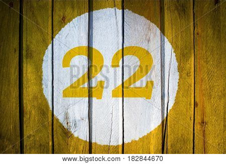 House Number Or Calendar Date In White Circle On Yellow Toned Wooden Door Background. Number Twenty