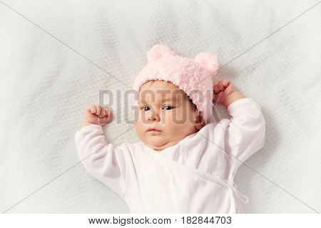 Cute newborn baby girl lying in the bed. Two month old infant child on white soft blanket