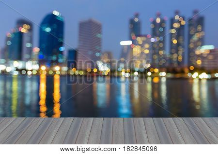 Opening wooden floor Twilight blurred bokeh office building with water reflection abstact background