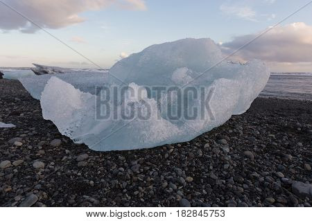 Ice breaking from glacier over black rock beach Iceland winter season natural landscape