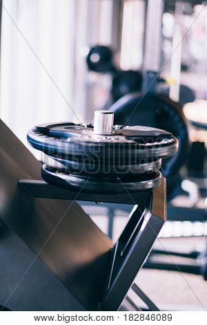 Set of metal barbells disks on barbbell holder in the fitness gym
