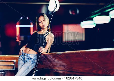 Young beautiful girl in a billiard club with cue stick posing