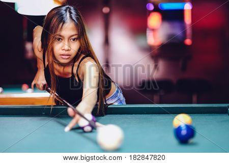 Young beautiful girl playing billiard in a club