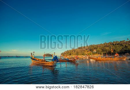 Longtale boat at the Thai beach. Paradice sand beach place. Boats on the clear water and blue sunrise sky