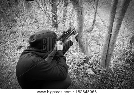 Close-up of man in hood aiming with sniper rifle shoot
