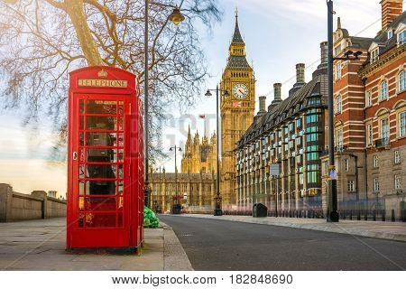 London England - The iconic british old red telephone box with the Big Ben at background in the center of London at sunset