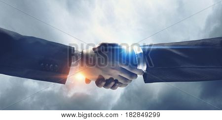 Business handshake as symbol of deal . Mixed media