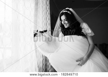 Beautiful Brunette Bride At Morning Gown With Wedding Dress At Room.