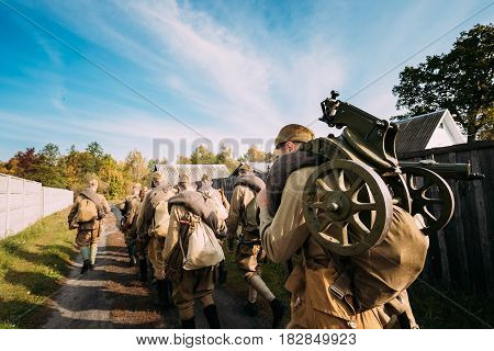 Group Of Re-enactors Dressed As Soviet Russian Red Army Infantry Soldiers Of World War II Marching Walking Along Country Road In Russian Village At Autumn Season.
