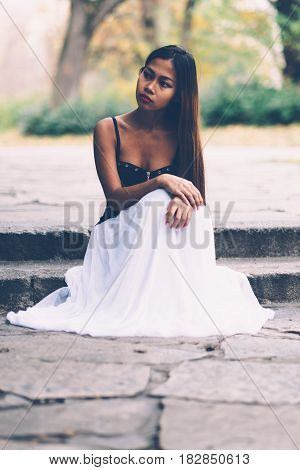 Young beautiful girl in white long dress sitting on the concrete floor.