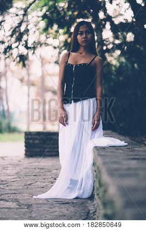 Beautiful girl in long white dress, posing in the park