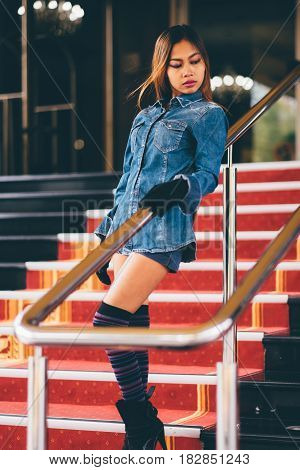 Young fashionable woman in blue jeans and long striped knee socks walking down on stairs with the red carpet