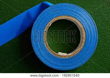 Blue industrial insulating tape on a green surface
