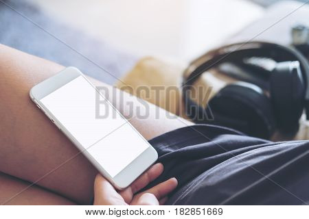 Mockup image of white mobile phone with blank white screen on woman's thigh with gray rug background in the house