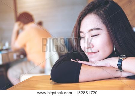 A beautiful asian woman sit with chin resting on her hands and closing her eyes in wooden cafe