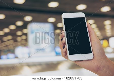 Mockup image of a hand holding and using white mobile phone with blank black screen while standing and waiting for baggage claim in the airport