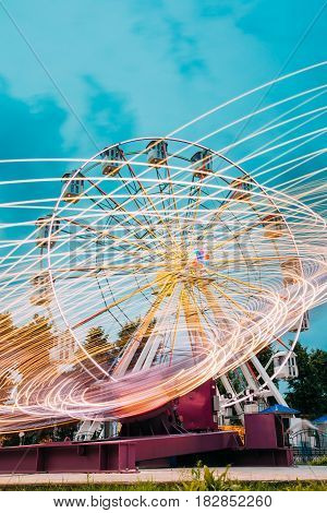 Motion Blurred Effect Around Of High Speed Rotating Illuminated Attraction Feature In City Amusement Park. Ferris Wheel On Summer Evening Blue Sky Background.