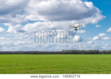 flying drone quadrocopter at the green field.