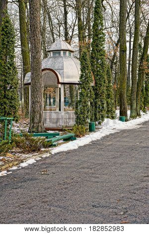 A gray gazebo among trees and a road in a winter park