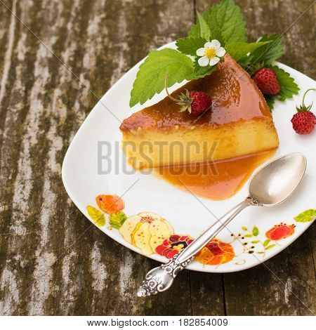 Slice of Milk Pudding with mint and strawberries over a wooden table. Brazilian Flan. French creme caramel dessert or flan with ingredients at the background. Custard pudding