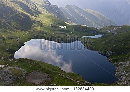 Clear mountain lake surface reflection in fagaras mountains, Carpathians, Romania