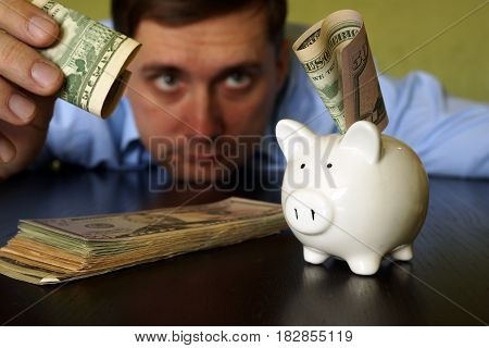 Man putting currency in piggy bank. Savings concept.