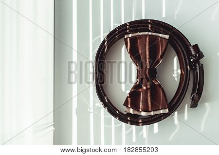 Brown bow tie and belt. Grooms wedding morning. Close up of modern man accessories on the window sills with shutters. Look from above