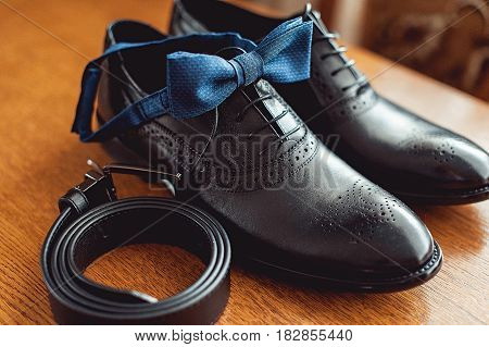 Close up of modern man accessories. Blue bow tie, leather shoes, and belt on a wooden table. Wedding morning