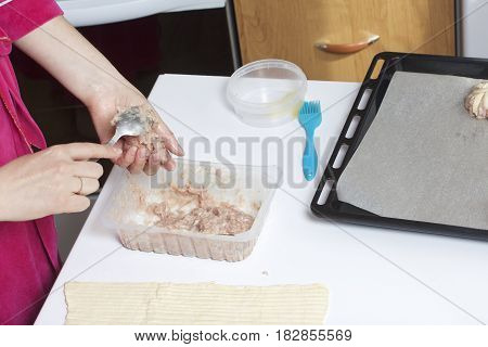 Stages Of Preparation Of Meat Glomeruli. A Woman Forms Minced Meat. Next To The Table Is A Dough And