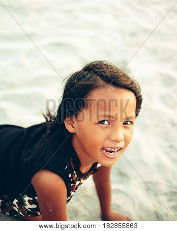 Playful little girl on the beach scrolling on the sand