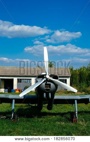 Gray airplane parked on the grass at the airfield