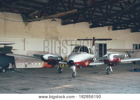 Modern white ultralight sport airplane in hangar