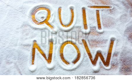Quit sugar now sign with wooden background