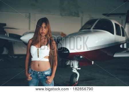 Beautiful Female Portrait In The Airplane Hangar, With Modern Aircraft