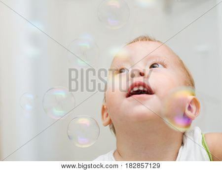 The little boy looks at flying soap bubbles..
