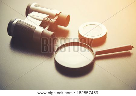 compass telescope and magnifier on black table