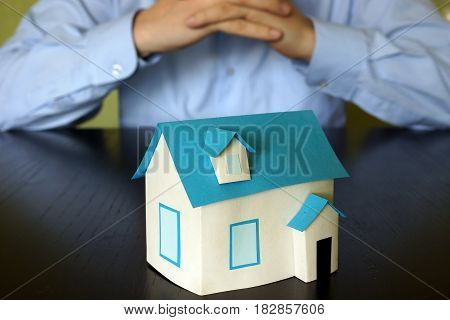 Real estate concept. Man is sitting at the table opposite house model.