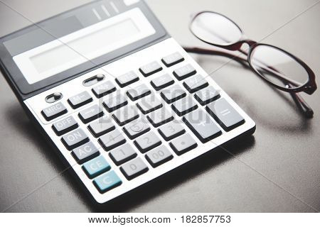 calculator and glasses on black table background