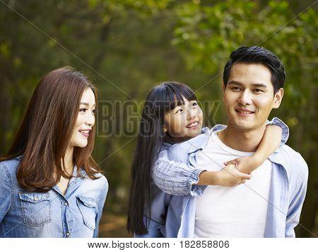 young asian family taking a walk enjoying nature.