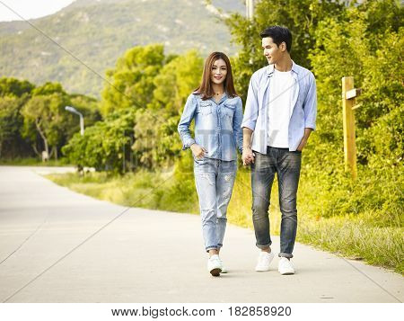 young asian couple walking on rural road.